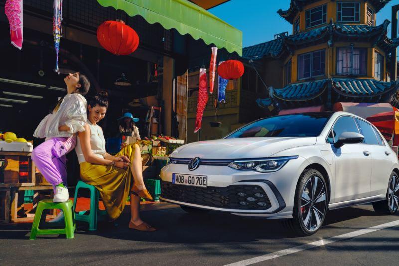 Dos chicas sentadas delante de un Volkswagen Golf 8 GTE aparcado frente a un puesto de un mercado