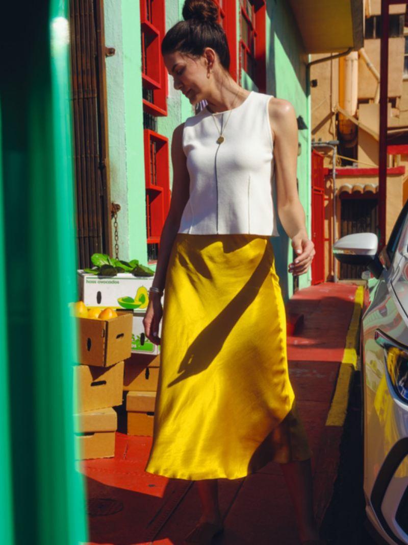 Chica de frente caminando frente a un puesto de un mercado junto a un Volkswagen Golf 8 GTE blanco que se ve parcialemente