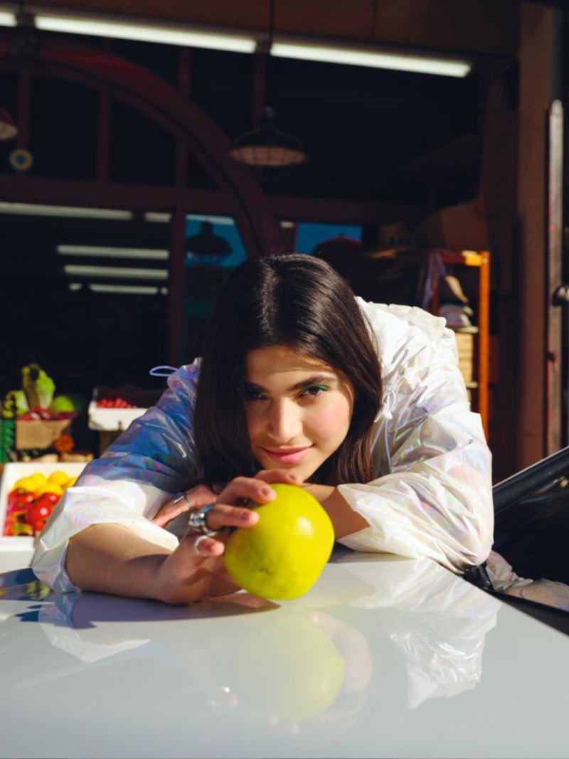 Chica mirando la cámara con una manzana verde en la mano apoyada en el capó de un Golf 8 GTE blanco