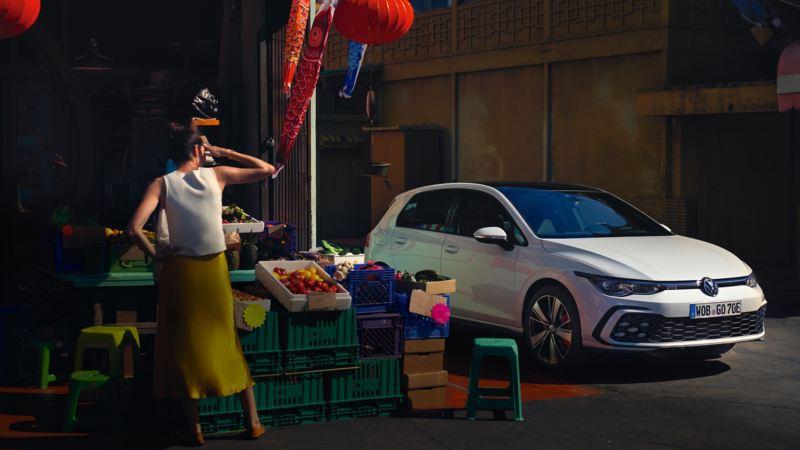 Volkswagen Golf 8 GTE blanco en la ciudad junto. un puesto de frutas