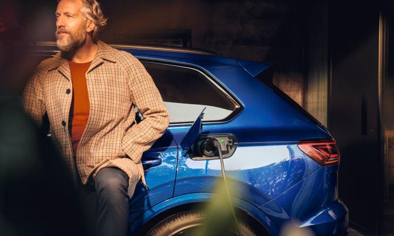 Hombre apoyado en un Volkswagen Touareg R azul conectado a la carga eléctrica