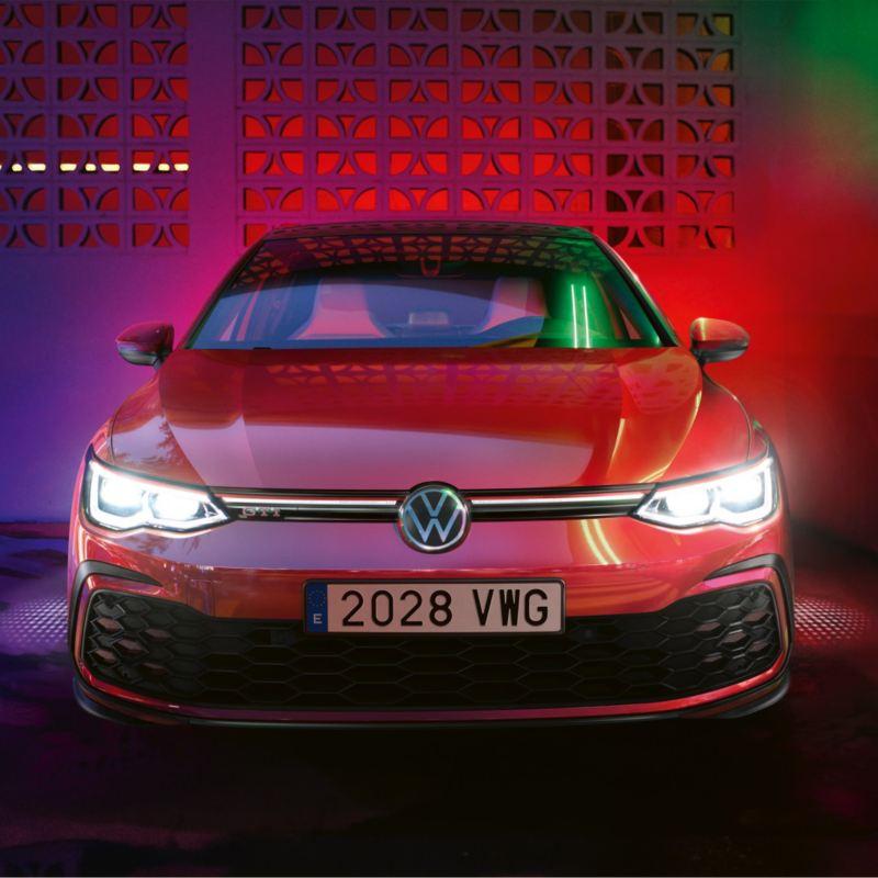 Volkswagen Golf 8 GTI rojo visto de frente e iluminado por focos de colores