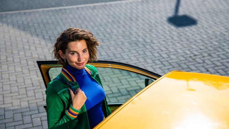 Mujer joven mirando al frente subiendo a un Volkswagen amarillo del que se ve parcialmente el techo
