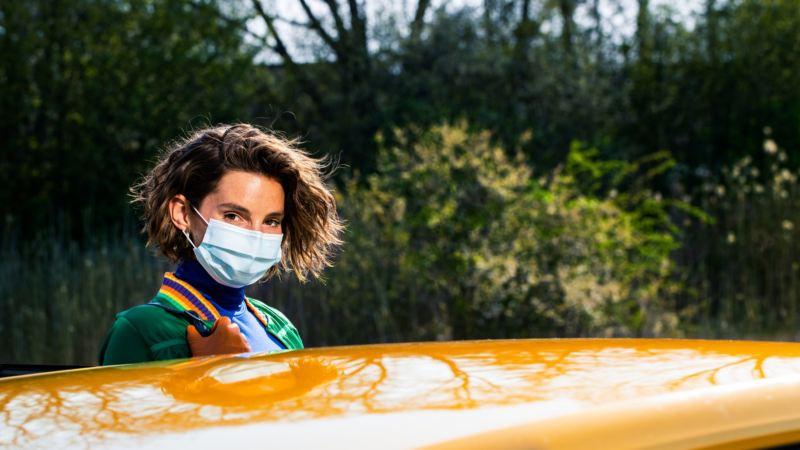 Mujer joven con mascarilla mirando al frente sobre el techo de un Volkswagen