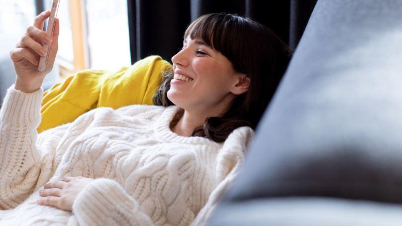 Mujer joven sonriendo sentada en un sofá mirando el móvil