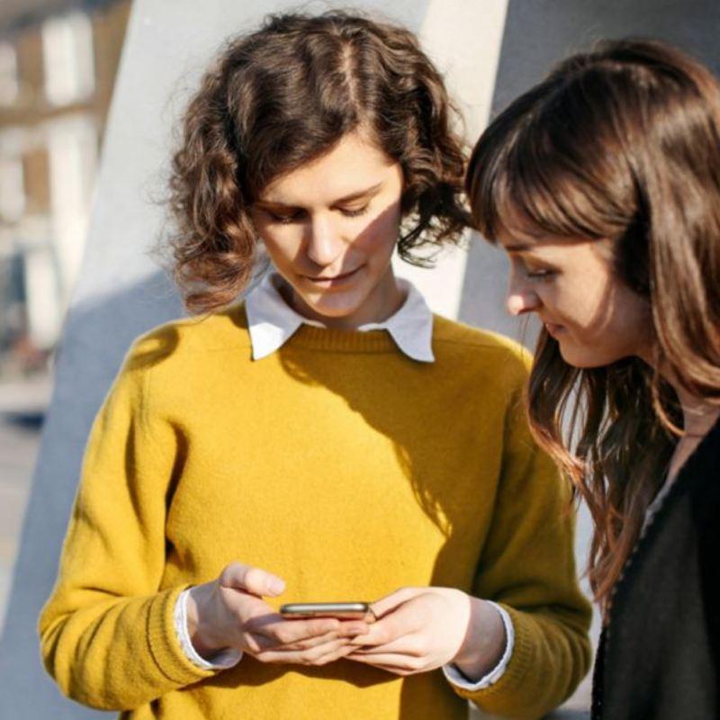 Dos mujeres jóvenes mirando un móvil