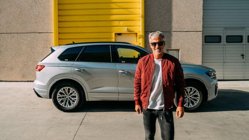Hombre mirando de frente delante de un SUV Volkswagen de color gris