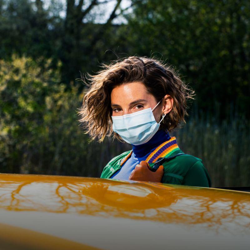 Chica con mascarilla mirando al frente sobre el techo de un Volkswagen