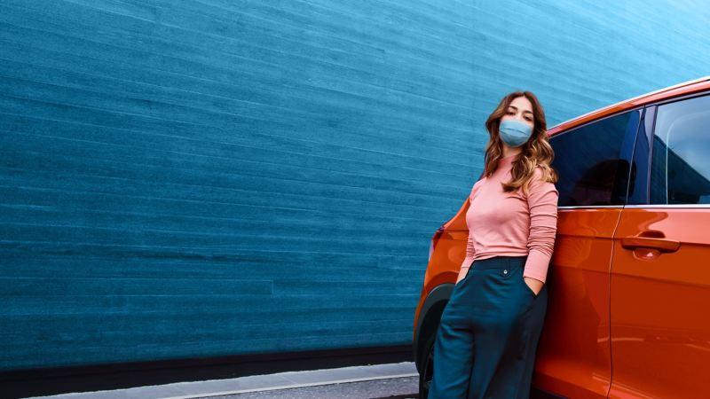 Mujer joven con mascarilla apoyada en un SUV Volkswagen frente a un muro verde