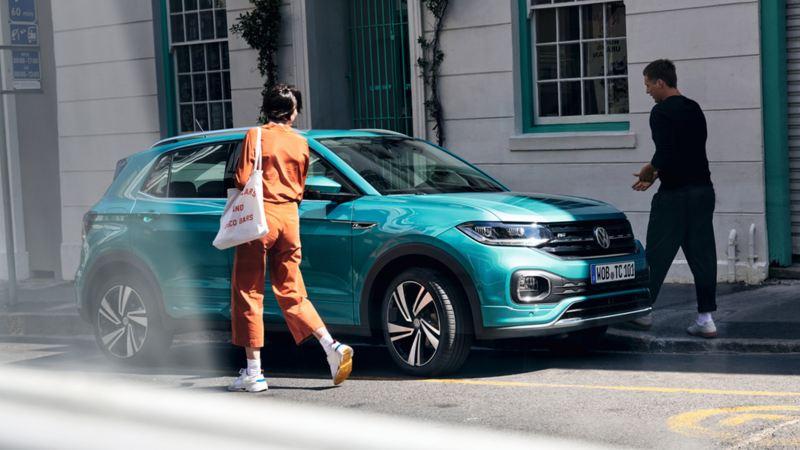 Pareja joven caminando hacia un Volkswagen T-Cross color turquesa aparcado en la calle