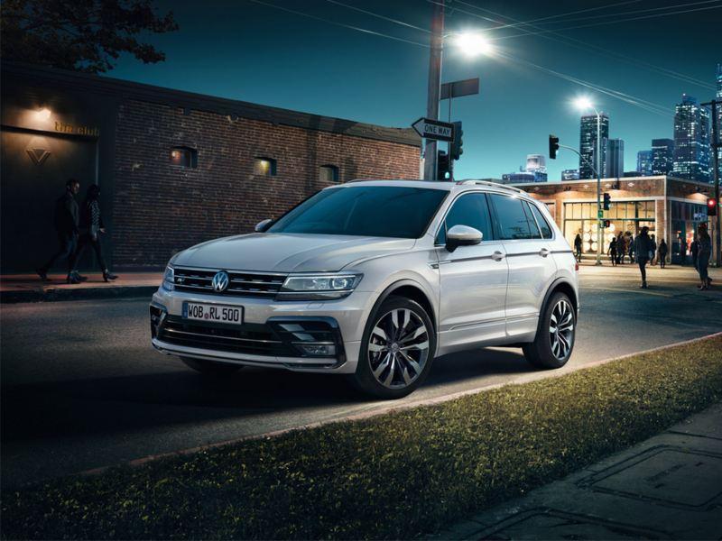 Volkswagen Tiguan blanco visto de frente aparcado en la ciudad de noche