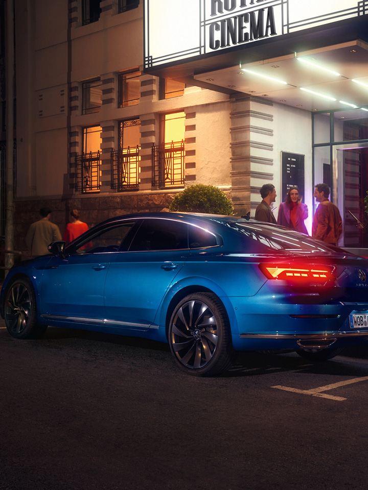 Nuevo Volkswagen Arteon azul aparcado en un portal frente a un grupo de gente