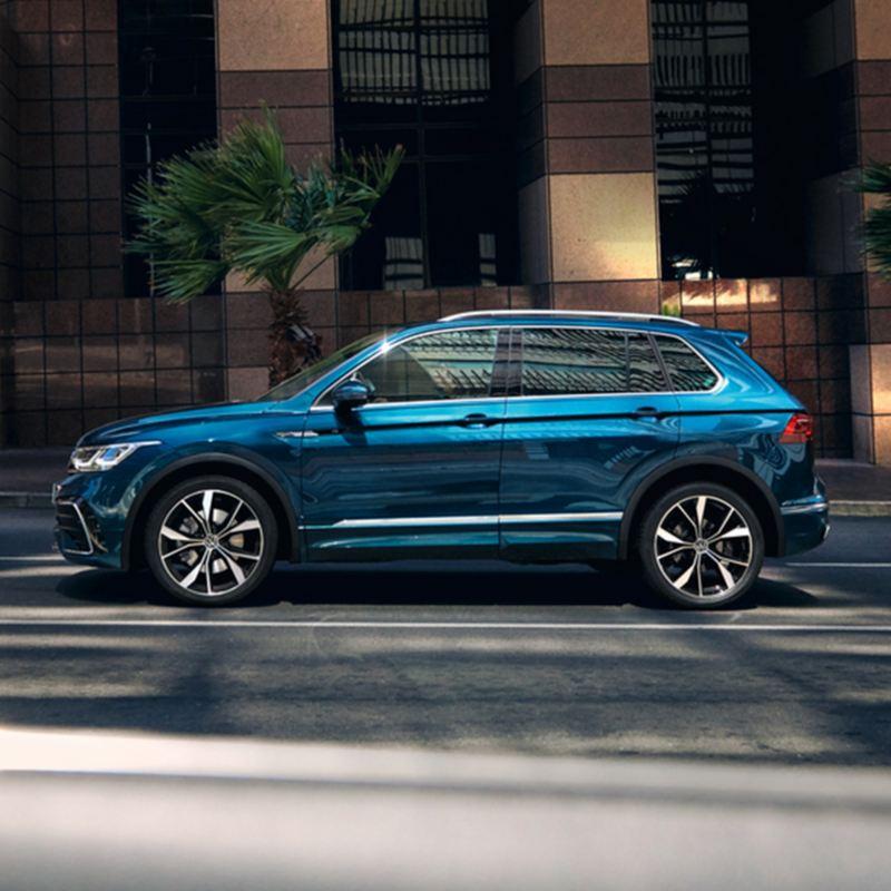 Nuevo Volkswagen Tiguan azul aparcado en la acera de una ciudad por el día
