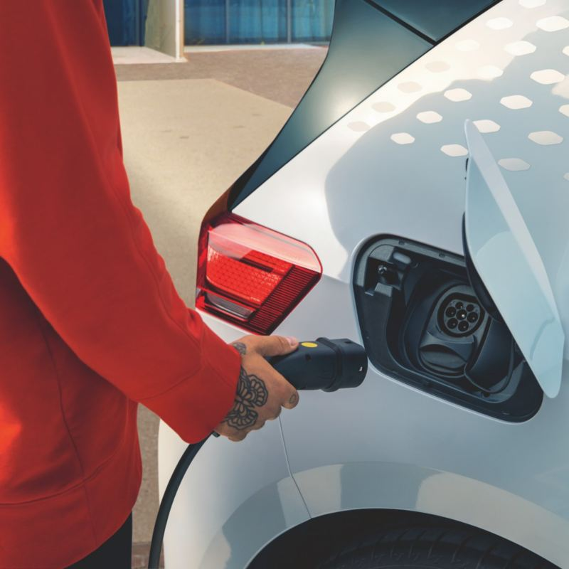 Chico sujetando el enchufe de carga junto a un Nuevo Volkswagen ID.3 blanco