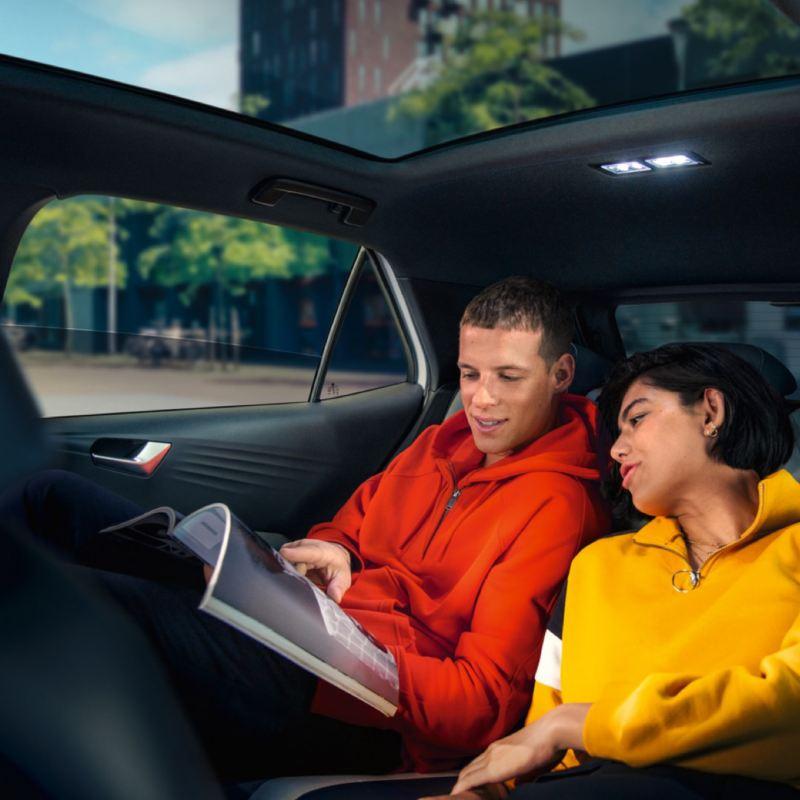 Una pareja de jóvenes leyendo en el asiento trasero de un ID.3