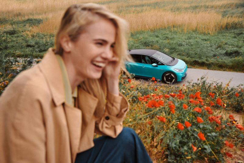 Chica en primer plano sonriendo en un campo de flores delante de un Volkswagen ID.3