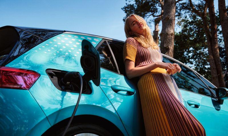 Chica apoyada en el costado de un Volkswagen ID. 3 verde con el cargador eléctrico conectado