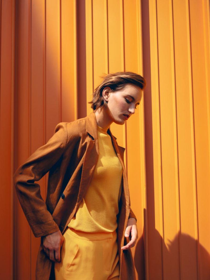 Chica mirando al suelo vestida de tonos ocres frente a una pared ocre