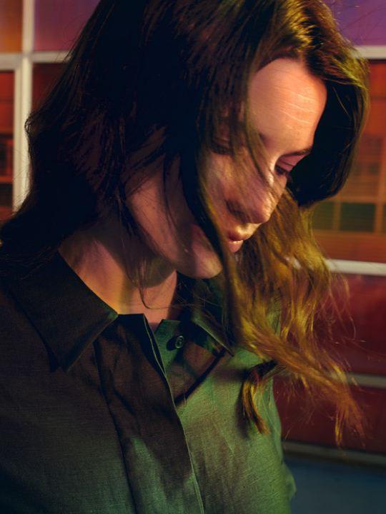 Chica con una blusa verde mirando al suelo frente a una cristalera