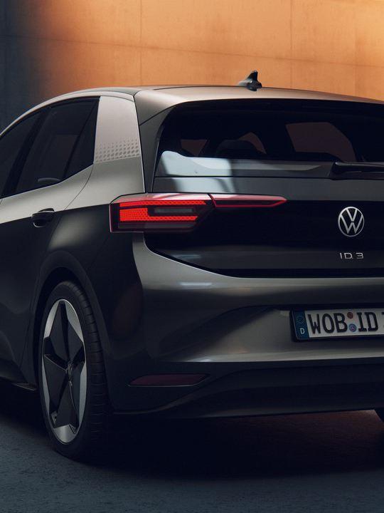 Vista en tres cuartos de un Nuevo Volkswagen ID.3 gris aparcado en un hangar en la penumbra