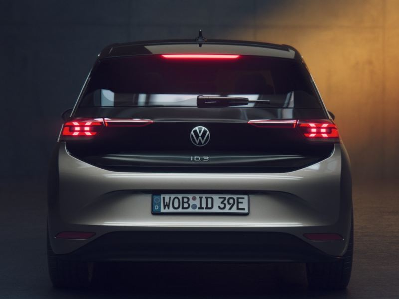 Vista trasera de un Nuevo Volkswagen ID.3 gris aparcado en un hangar en la penumbra