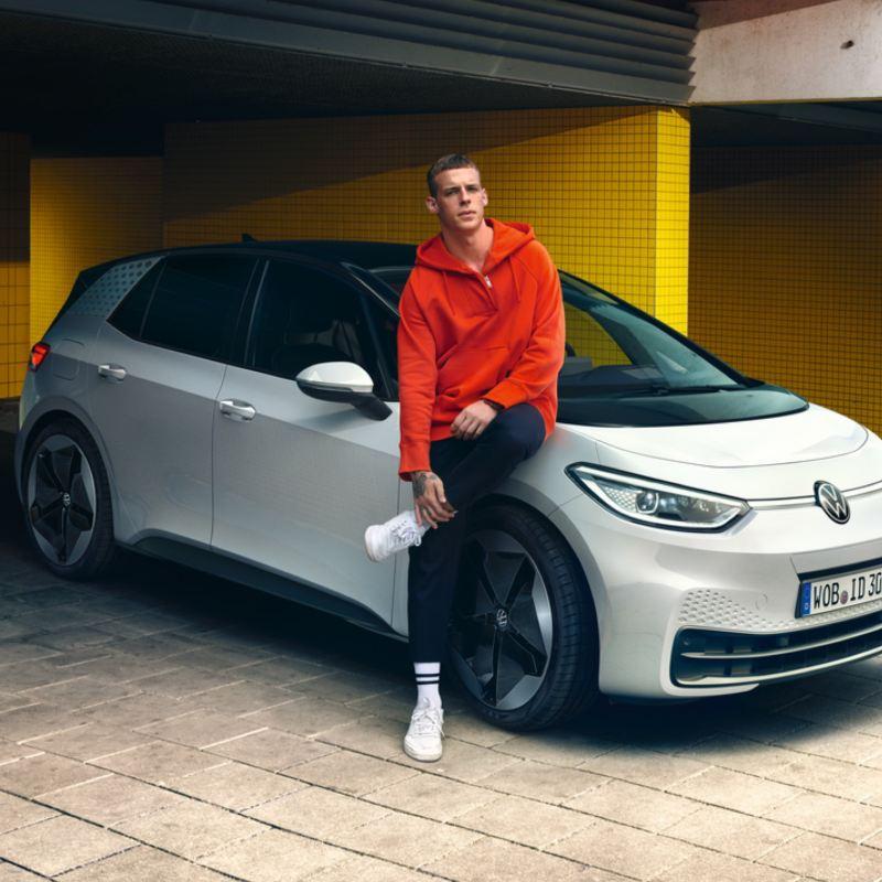 Hombre joven mirando a la cámara apoyado en un Volkswagen ID.3 en un parking
