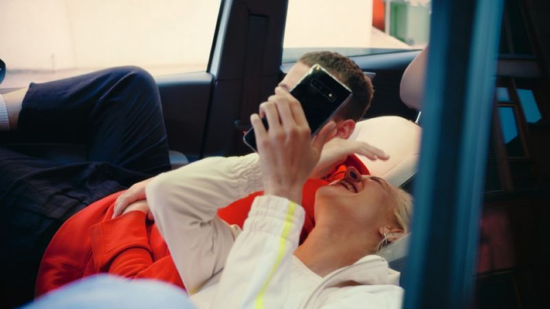 Chica riéndose tumbada en los asientos reclinables de un Volkswagen ID.3