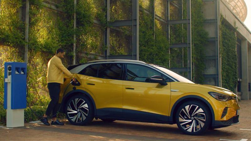 Hombre conectando un Volkswagen ID.4 amarillo a un punto de carga