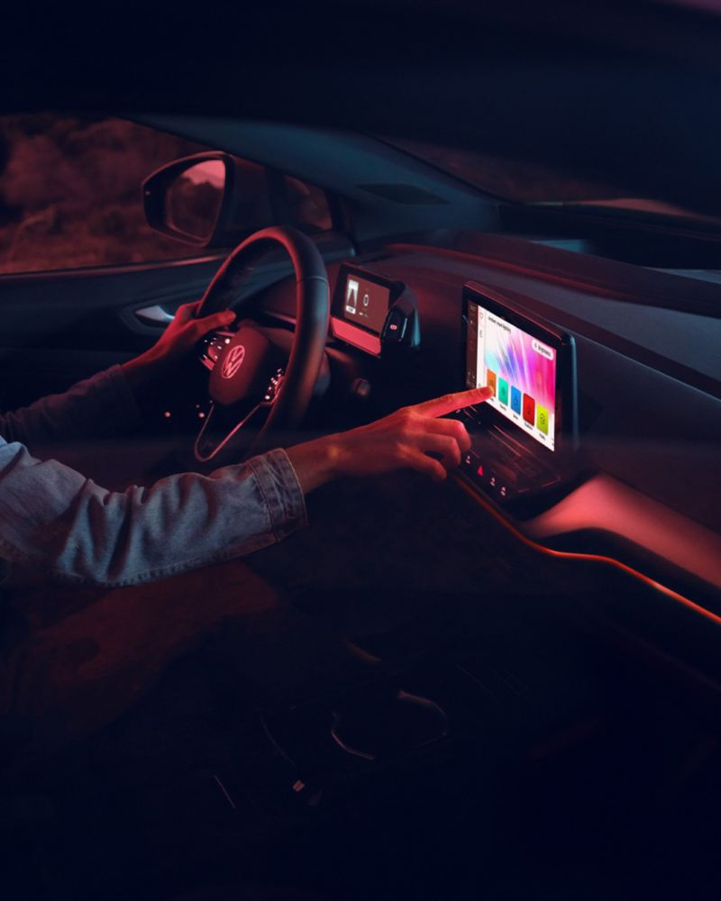 Detalle de un conductor seleccionando la iluminación ambiental en la pantalla de un Volkswagen ID.4