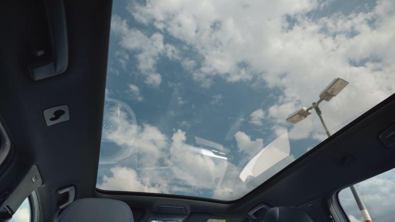 Hombre al volante de un Volkswagen ID.4 con vista al techo solar panorámico