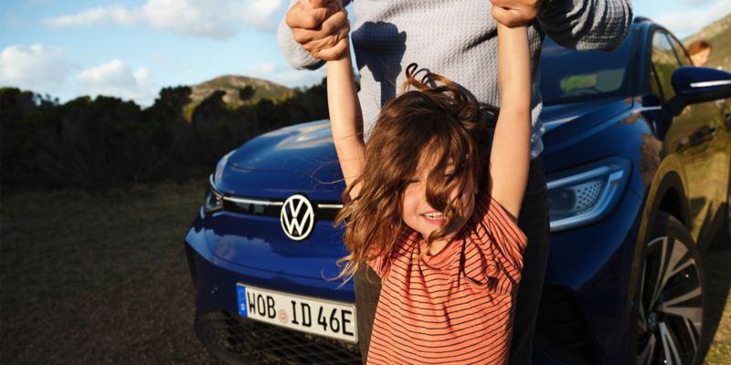 Una niña sonriendo tomada de los brazos por su padre delante de un Volkswagen ID.4 azul en la montaña