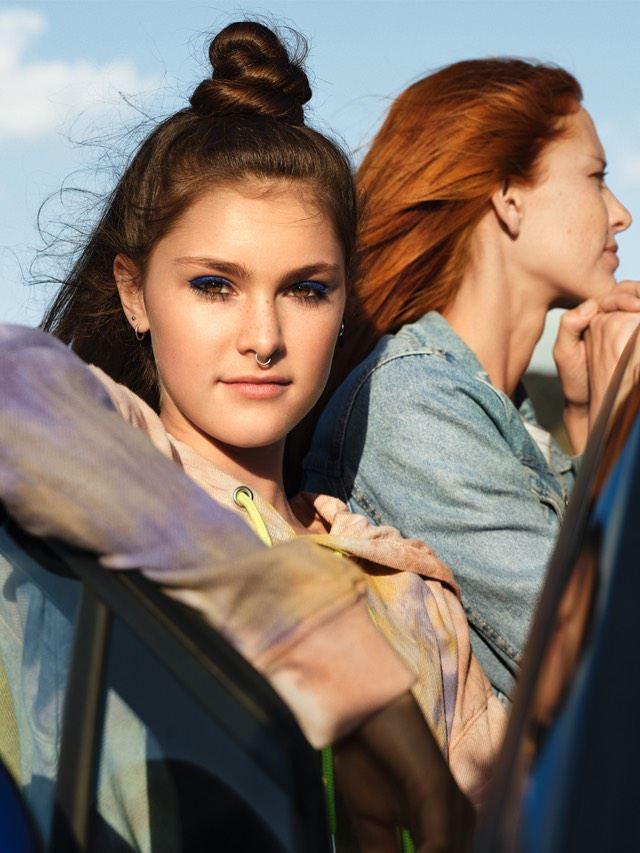Chica joven con su madre apoyada en la puerta abierta de un Volkswagen ID.4