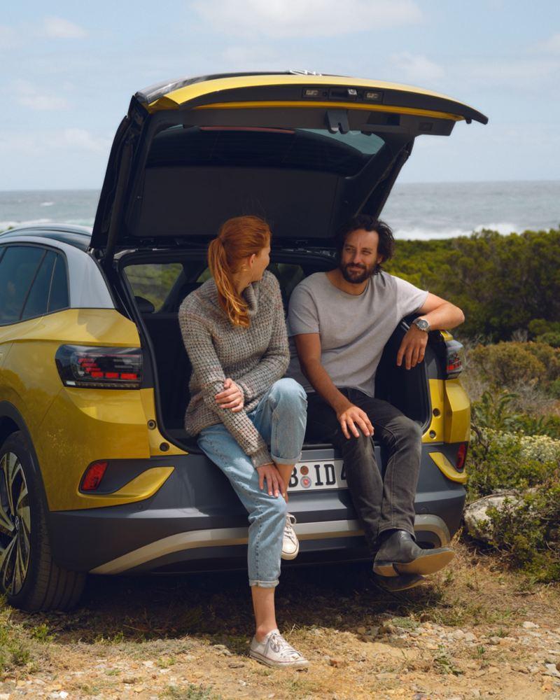 Un Volkswagen ID.4 con la puerta trasera abierta y una pareja sentada en ella