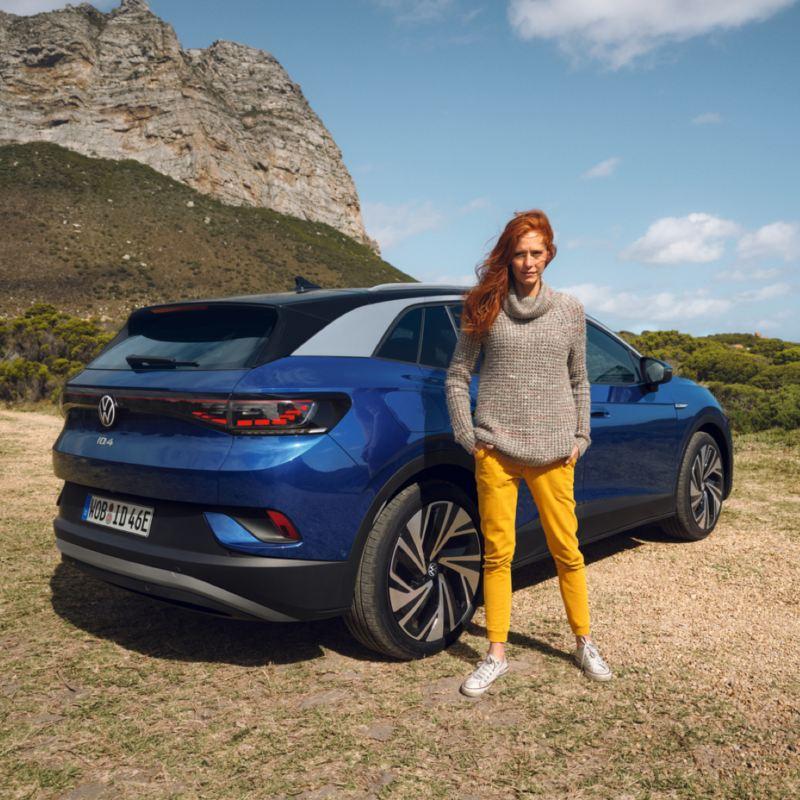 Chica de pie delante de un Volkswagen ID.4 azul visto de atrás aparcado en la montaña
