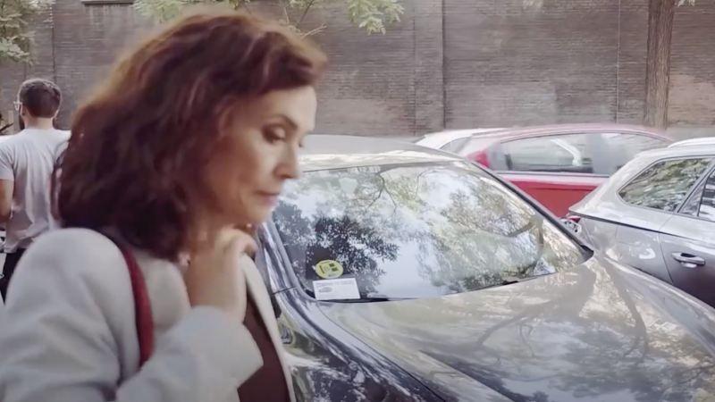 Secuencia de una mujer andando por la calle junto a un Volkswagen con etiqueta de eficiencia