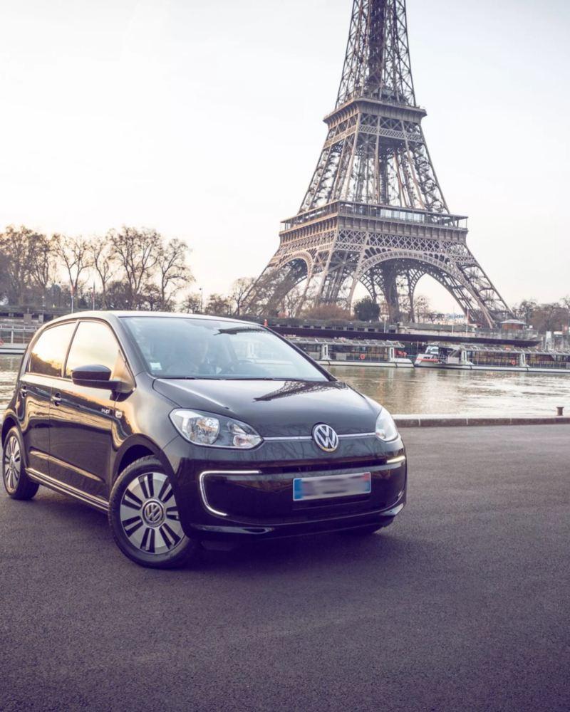 Volkswagen e-up! negro aparcado junto al río Sena con la Torre Eiffel de fondo