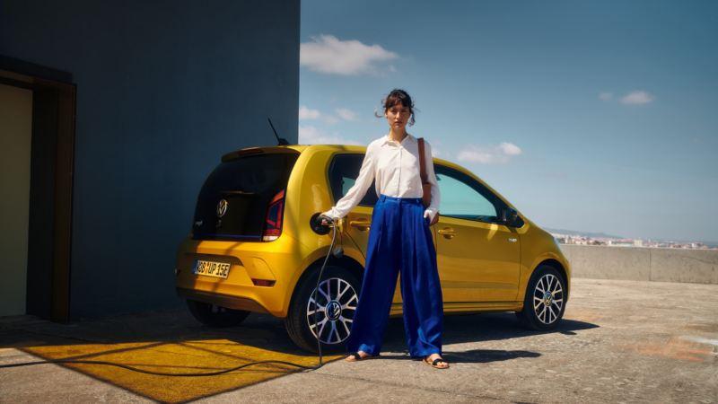 Mujer mirando la cámara y cargando un Volkswagen e-up! amarillo