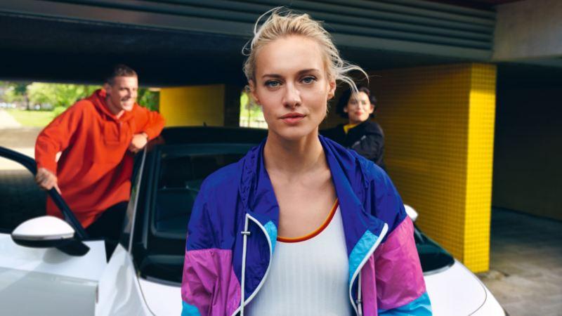 Chica joven mirando a la cámara delante de in Volkswagen ID.3 con una pareja