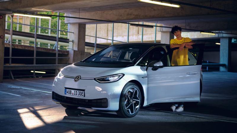 Un joven con camiseta amarilla de pie junto a un Volkswagen ID.3 con la puerta del conductor abierta
