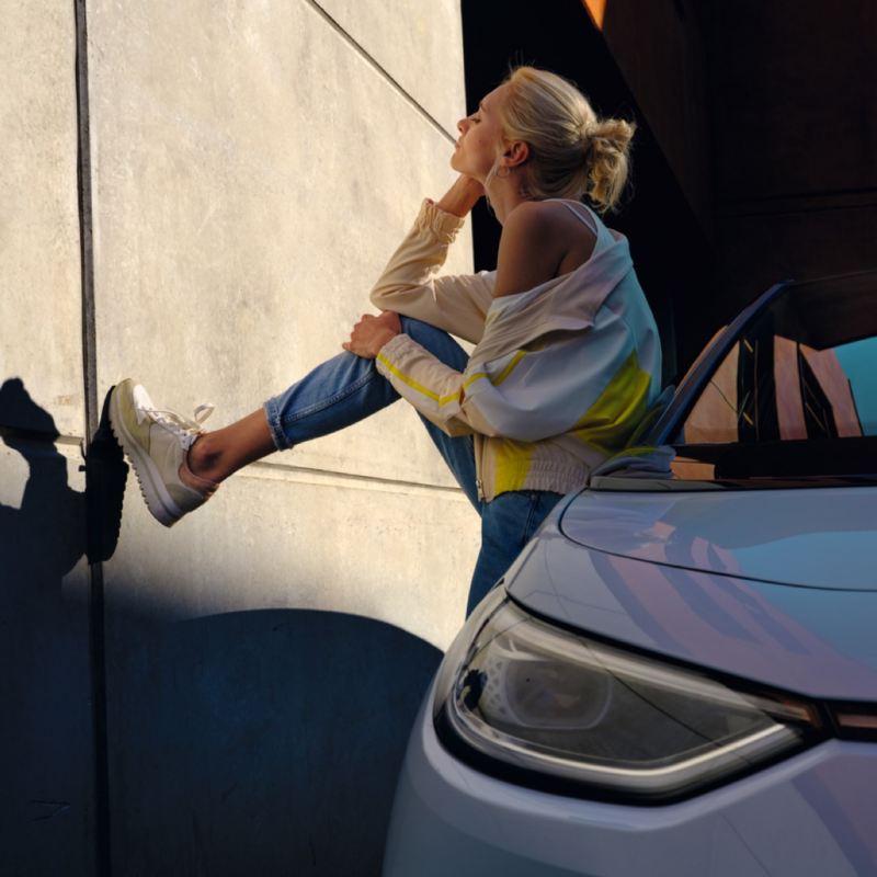 Chica apoyada en un Volkswagen ID.3 vista de costado con un pie en la pared