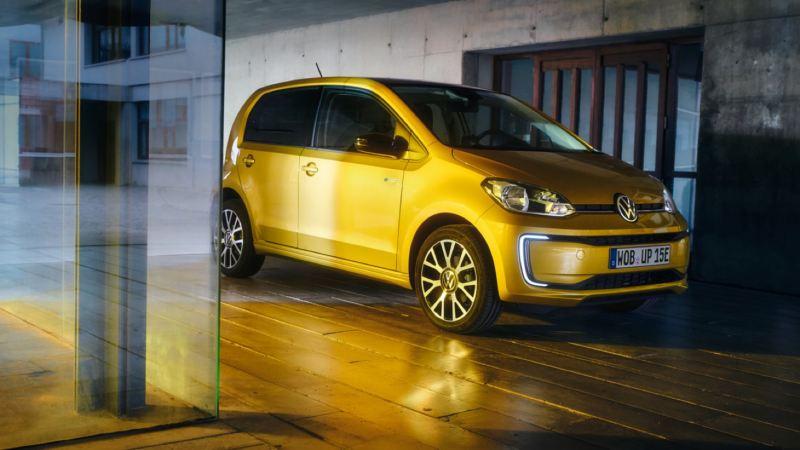 Volkswagen e-up! amarillo aparcado frente a la puerta de una casa