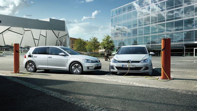 Dos Volkswagen e-Golf blancos conectados a cargadores eléctricos en la calle