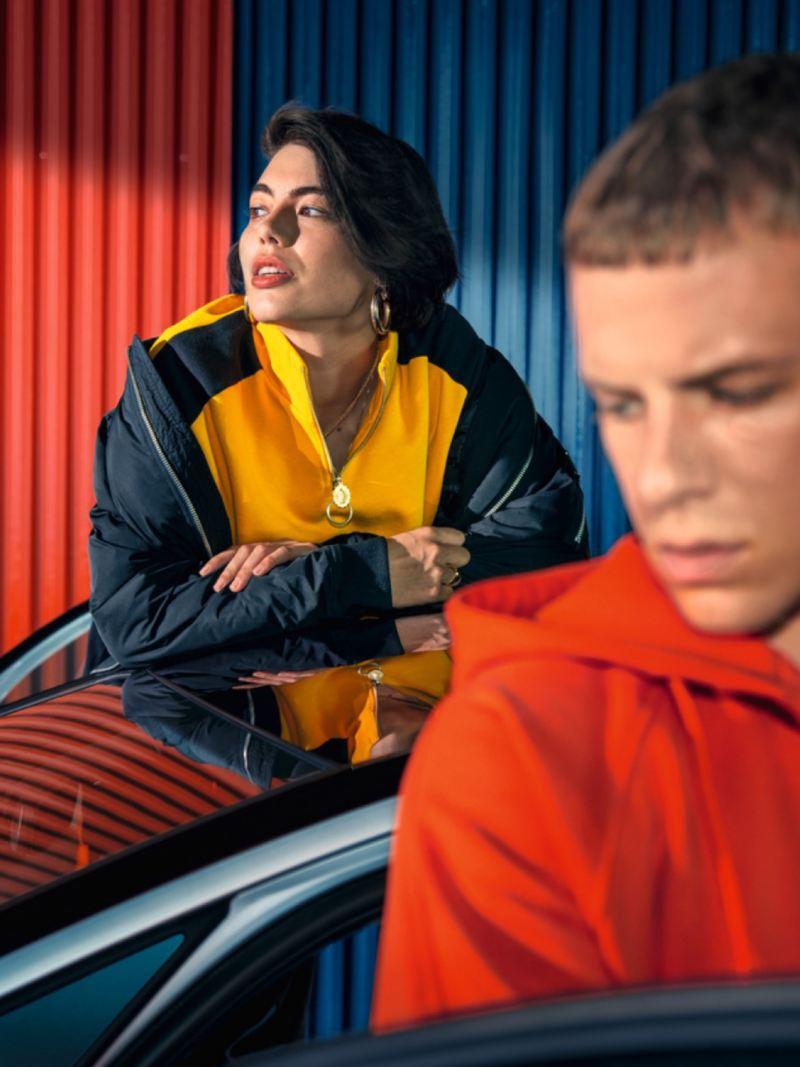 Mujer joven apoyada en un Volkswagen eléctrico y un chico de naranja desenfocado en primer plano