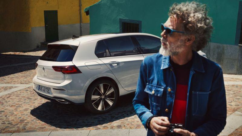 Volkswagen GTE blanco visto de costado y un hombre con barba fuera de foco en primer plano