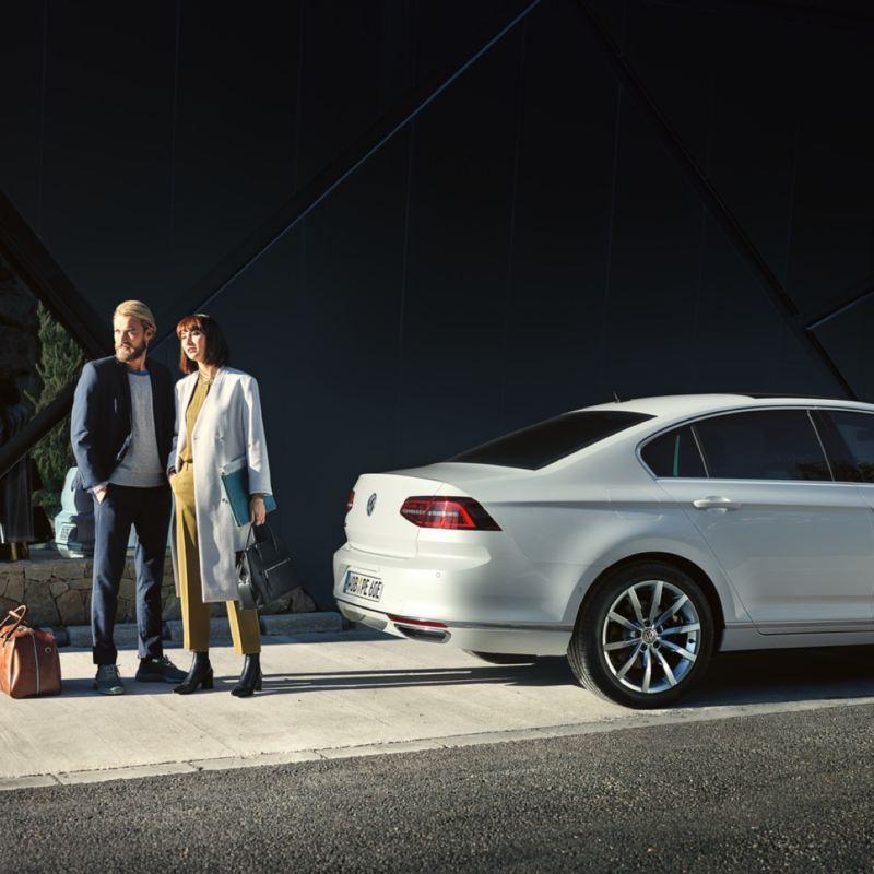 Pareja de pie detrás de un Volkswagen Passat GTE blanco aparcado