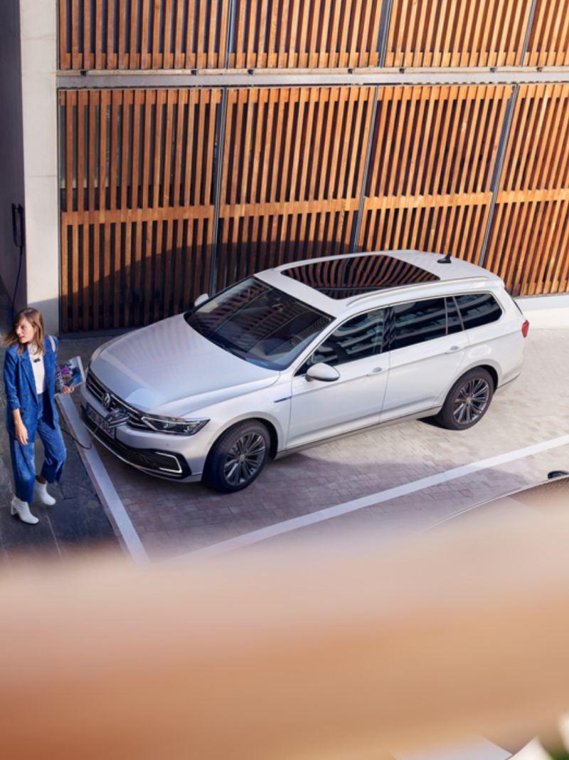 Pareja con una niña delante de un Volkswagen Passat Variant GTE conectado a un cargador eléctrico