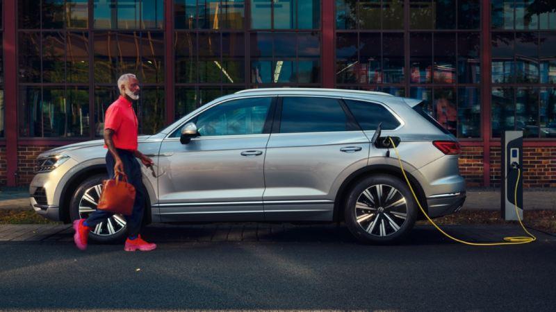 Volkswagen Touareg eHybrid gris conectado a un cargador eléctrico en la calle mientras un hombre camina delante