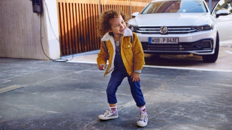 Una niña con chaqueta amarilla delante de un Volkswagen Passat GTE blanco aparcado en casa