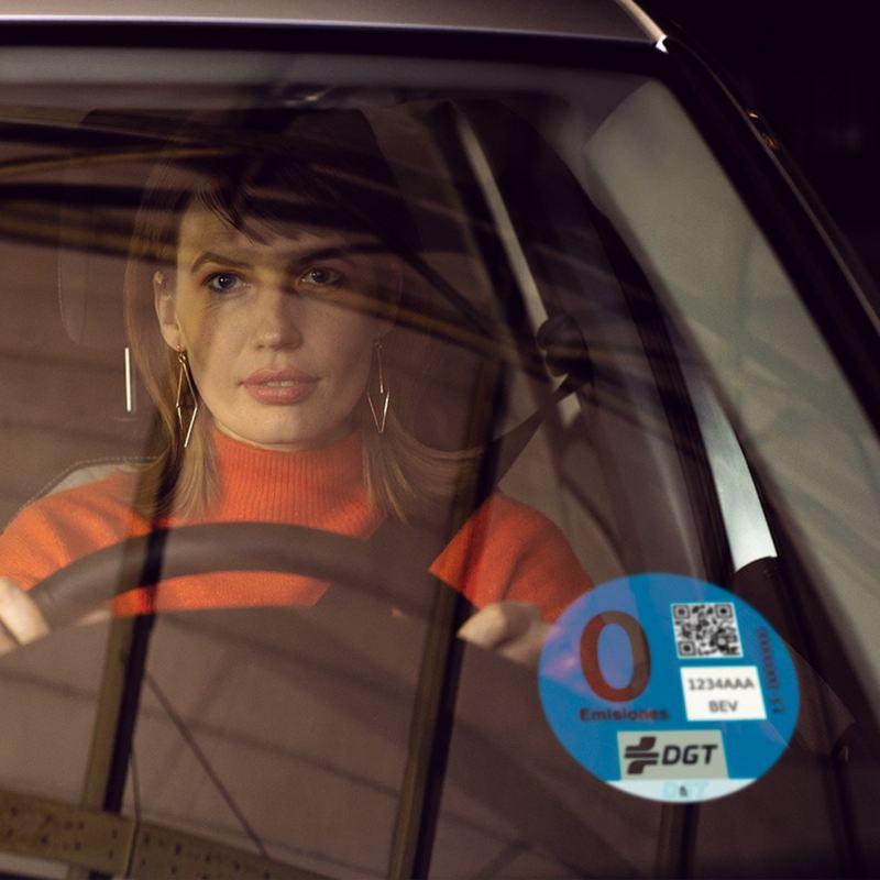 Mujer al volante de un Volkswagen GTE vista a través de un parabrisa con el distintivo de 0 emisiones de la DGT