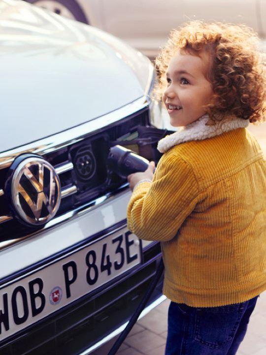 Niña con chaqueta amarilla conectando el cargador eléctrico a un Volkswagen Passat GTE blanco